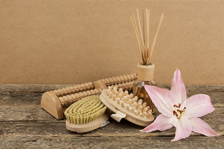 Beautiful composition with aromatic oil, pink lily and massage brushes on wooden background, weight loss and body care concept