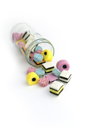 Small glass jar with colored chewing sweets