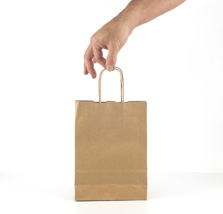A mans hand gently with his fingers holds a kraft paper bag