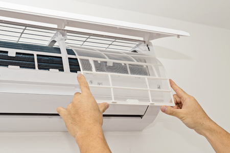 Cambiando el filtro en el aire acondicionado El concepto de una vivienda segura y saludable Foto de archivo - 87696688
