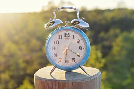 Vintage blue alarm clock on summer forest background. Daylight saving time concept winter time 스톡 콘텐츠