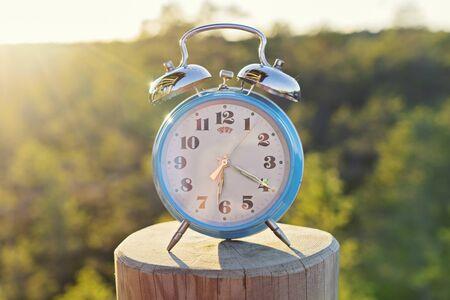 Vintage blue alarm clock on summer forest background. Daylight saving time concept winter time Foto de archivo