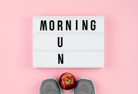 Motivation quotes on light box, apple and sport shoes on the pink background Healthy lifestyle concept Archivio Fotografico