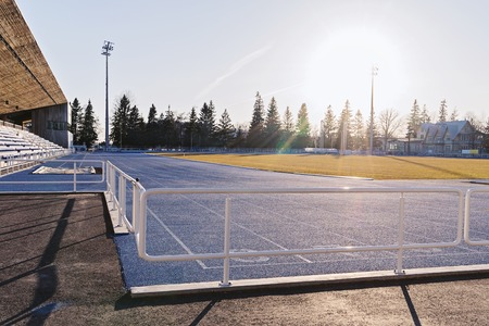 View of empty open outdoor stadium in morning sunrise light. Active lifestyle concept