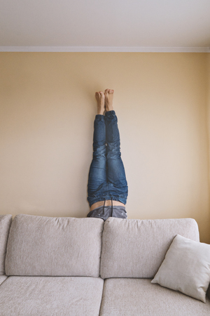 Man handstanding behind couch, yoga and spring cleaning concept, furniture care