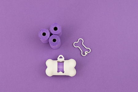 Pet dog waste poopbag dispensers and holders, bags for poop and white holder dispenser on violet background. Top view Stock Photo