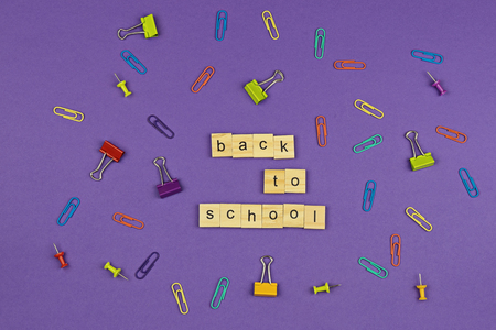 BACK TO SCHOOL text on wooden letters on violet background with colorful stationery items. Concept for beginning of academic year Stock Photo
