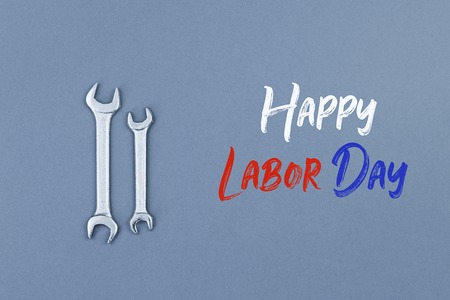 Greeting card to celebrate Labor day American public holiday. Vintage spanners on gray grey background with text Stock Photo