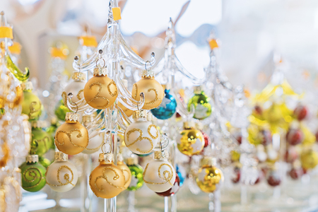 Colorful transparent glass Christmas trees in glass souvenir shop, soft and selective focus