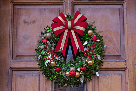 Traditional Christmas fir wreath with red ribbon, Christmas balls and bells. Decoration of the front door on the threshold of Christmas