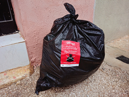 Valletta, Malta - October 31, 2018: Black waste bag on street with red notice about waste collection schedule. From October 31, 2018 in Malta are new requirements and rules for sorting household waste