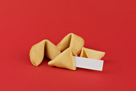 Traditional Chinese new year fortune cookies on red background with white paper for mottos