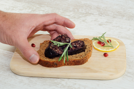 Male hand take sandwich with rye bread and sliced blood sausage on wooden plate 스톡 콘텐츠 - 113806566