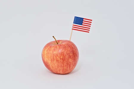 Ripe red apple and small American flag canape on white background. Greeting card for celebration of President's Day in America concept