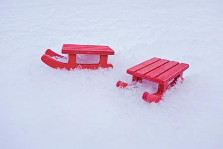 Miniature red sled on white snow with copy space