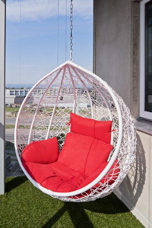 View of a modern cozy hanging chair with red pillows on a balcony with great view in town