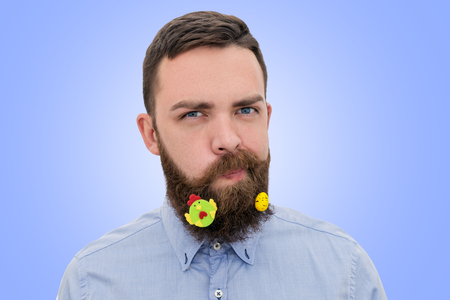 Portrait of handsome bearded man with decorated beard for Easter on blue background. Happy Easter greeting card concept