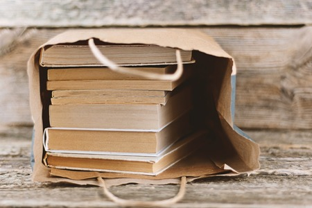 Stack of old books in paper bag on wooden background. Bookstore and Fair Concept sale, World book day, copy space