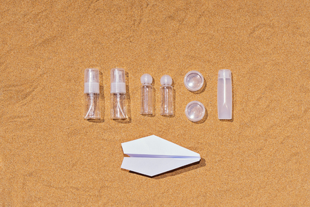 Travel set of containers for hand luggage cosmetics on an airplane with a permitted volume of up to 100 ml. Top view of cosmetic plastic containers for traveling in an airplane on sandy background Stock fotó