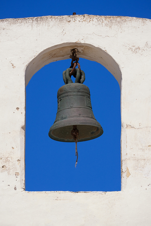 Church bell on a white bell tower against a blue clear sky, closeup long angle view