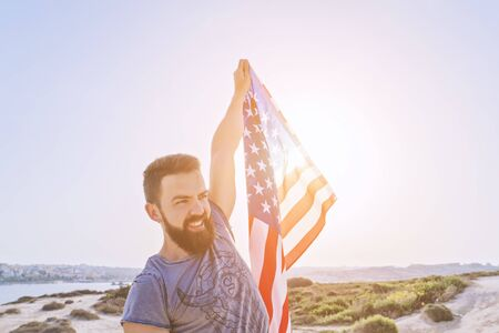 Independence day United States of America. Smiling bearded man holding in raised hand American Flag against sunset sky, outdoor. National flag day of USA or Memorial day concept Foto de archivo - 127561848