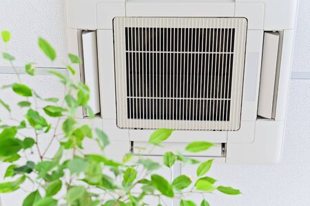 Ceiling air conditioner in modern office or at home with green ficus plant leaves an idea of clean air. Indoor air quality concept Imagens
