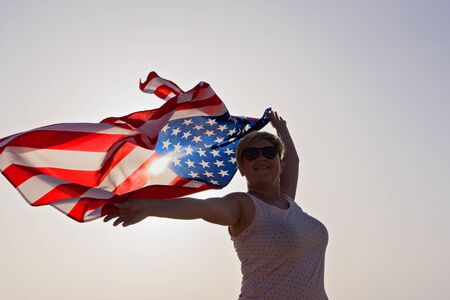 Silhouette of smiling woman in sunglasses with raised hands and waving flag of United States of America against sunset sky Foto de archivo - 127561896