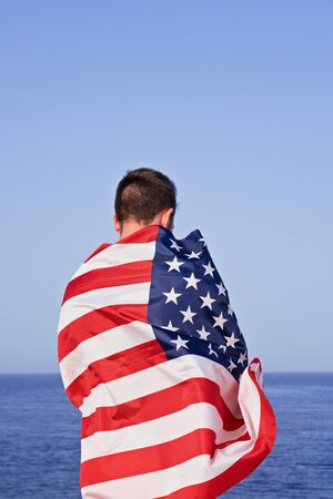 Independence day of United States of America. Adult Man from behind wrapped in American Flag stand against clear blue sky Foto de archivo - 127561951