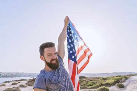 Independence day United States of America. Smiling bearded man holding in raised hand American Flag against sunset sky, outdoor. National flag day of USA or Memorial day concept Foto de archivo - 127561965