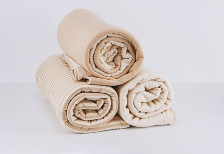 Closeup pile wrapped folded natural beige cotton blanket for kid on white background Foto de archivo - 127562746