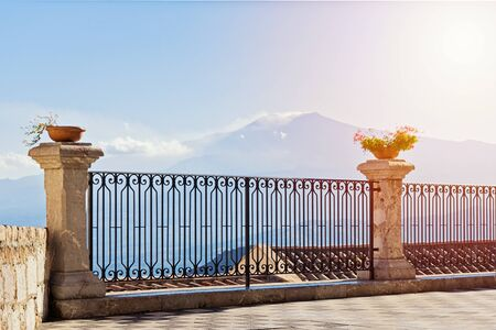 Scenic view of the smoking volcano Etna from the street of Castelmola with vintage fence and potted flowers Foto de archivo - 127562777