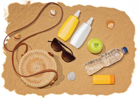Beach accessories, rattan bag, bottle of water and sunglasses on beach sand. Sea beach and summer concept Foto de archivo - 127562901