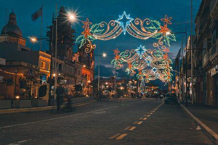 Festive Christmas illumination and decorations on streets of Paola, Malta. Urban street with Christmas illuminations. Xmas lights and people walking around on the street Foto de archivo - 127562915
