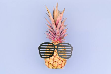 Funny yellow pineapple face with glasses on purple background. Back to school or sale school stationery concept template Фото со стока