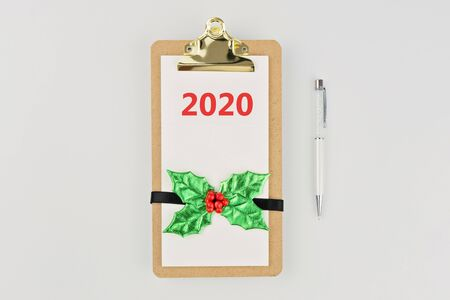 Empty notebook clipboard with Christmas decor and pen on white background with copy space, flat lay style. New beginnings planning concept, template Foto de archivo - 127562940