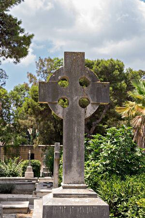 Old tombstone with Celtic cross an ancient war cemetery, Malta Foto de archivo - 127562971