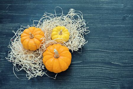 Three ripe ornamental pumpkins lie in straw on wooden background. Template for celebration of Halloween and Thanksgiving. Flat lay, copy space Foto de archivo - 127562983