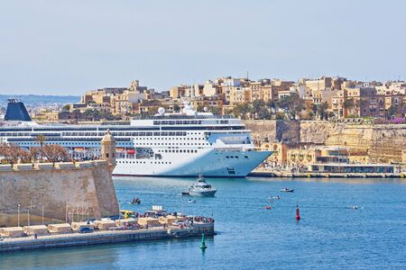 General view of Valletta Grand harbor in Malta with large cruise liner ship in sea bay Фото со стока