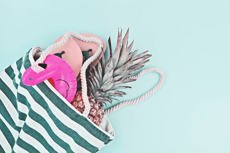 Summer beach set flat lay. Floated flamingo, flip-flops, pineapple on blue background, top view, copy space. Summer time routine and holiday concept Zdjęcie Seryjne