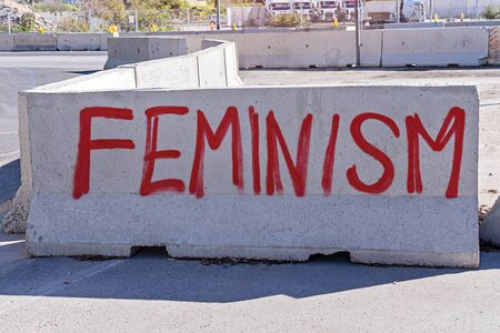 FEMINISM word is written on concrete barrier with paint spray on city street. Illegal street graffiti concept