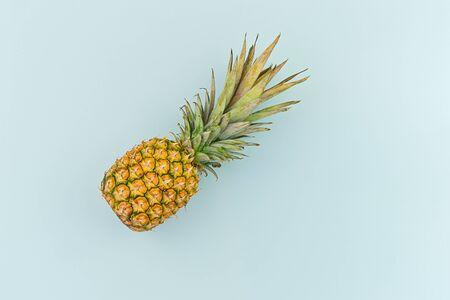 Ripe pineapple on blue background in minimalism style, flat lay and copy space Zdjęcie Seryjne - 129191969