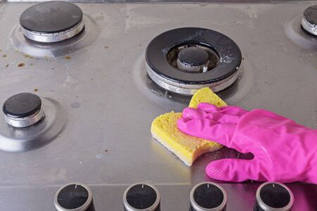 Manual Cleaning of stainless steel gas stove with scrub and sponge Stockfoto