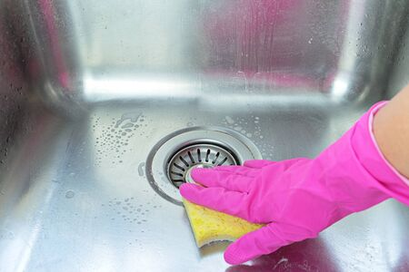 Hand in pink rubber glove clean and polishing stainless steel sink with sponge and dirt remover. Homework and cleaning plumbing concept