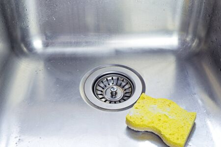Cleaning polished stainless shiny sink with scrub sponge in kitchen, above view. Homework and cleaning plumbing concept