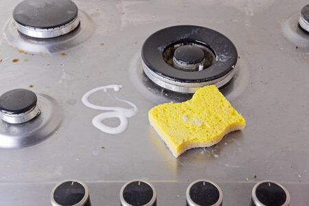 Manual Cleaning of stainless steel gas stove with scrub and sponge 스톡 콘텐츠