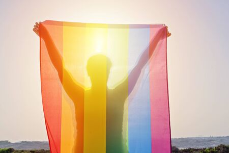 Young woman holding raised hands waving LGBT rainbow flag against sky. Happiness, freedom and love concept for same sex couples