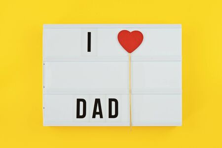 Happy Fathers Day flat lay. Lightbox with text i love dad on yellow background with red heart. Greeting card to celebrate Fathers day