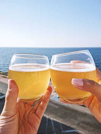 Hands holding glasses with cold beer against blue sky, closeup view Outdoor celebration and cheers concept
