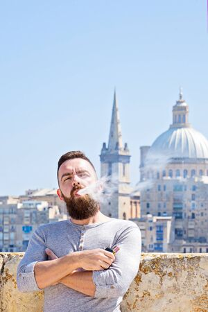 Portrait of caucasian mid-adult man smoking electronic cigarette, standing by retaining wall against Valletta cityscape