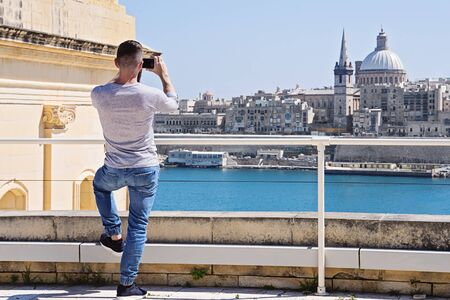 Caucasian student man behind with smartphone take photo of Valletta skyline cityscape